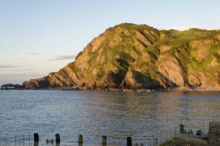 Late Sun on Beacon Point viewed from Harbour, Ilfracombe, Devon, UK