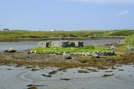 Ruined building on island in muddy sea loch, Benbecula 版權商用圖片