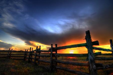 paisaje rural: puesta de sol hermosa de madera vieja fencewith