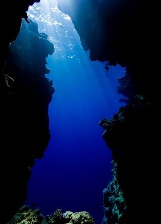 cueva: Rayos de sol se filtran desde la superficie del mar a través del agua azul claro en la salida de una cueva submarina