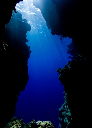 Sun beams filter down from the sea surface through clear blue water onto the exit of an underwater cave