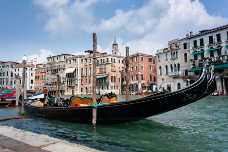 A traditional Gondola moored on the side of the Grand Canal in Venice