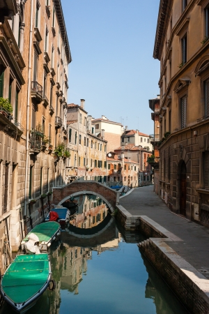 Small canal with boats, bridge and a building reflected in its clear waters in the city of Venice Stock Photo - 16791304