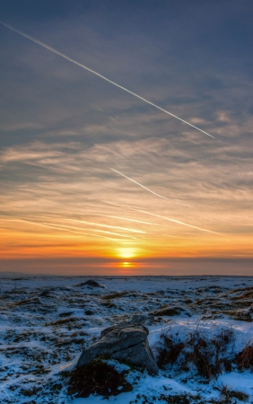 Sunset over a snowy empty moorland in winter photo