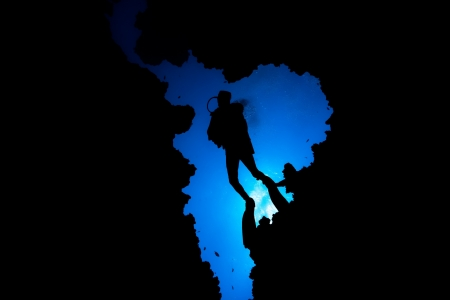 Silhouette of a diver dropping into an underwater cave