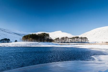 sub zero: A frozen lake in a mountainous snow covered landscape Stock Photo