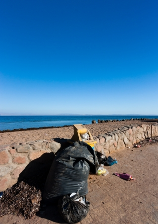 Overflowing abandoned bins and garbage bags left next to a tropical beach photo