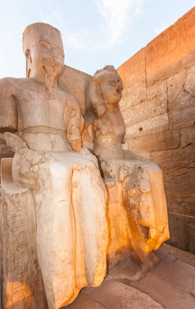 Ancient Egyptian statues lit by artificial light in the early evening at the Karnak Temple, Luxor