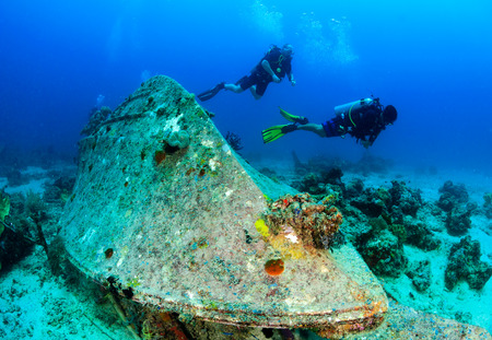 upturned: SCUBA divers around an upturned underwater wreck