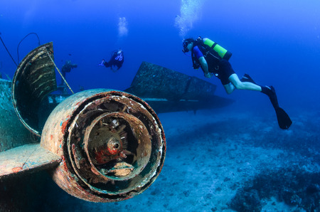 SCUBA divers explore the engine area of an underwater plane wreck photo