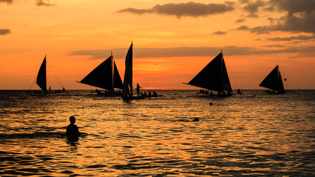 Silhouettes of people and sailing boats against an orange tropical sunset photo