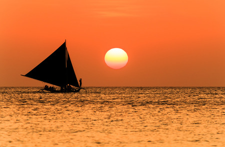 Traditional sailing boat and a tropical sunset photo
