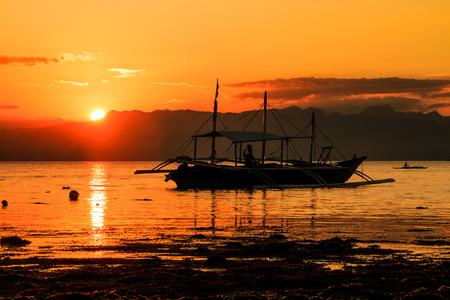 Sun setting behind a mountain reflected on a calm ocean