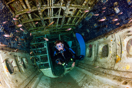 A SCUBA diver explores the upturned cabin of an underwater aircraft wreck