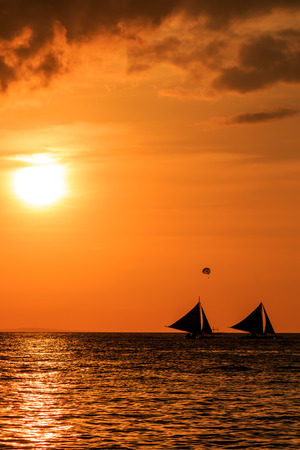 Traditional sailing boats in silhouette at sunset photo