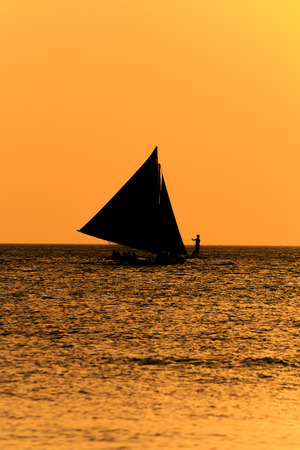 A traditional sailing banca on a calm ocean with a vivid orange sunset photo
