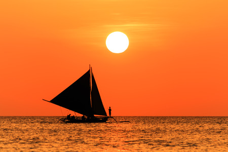 Traditional sailing boat and a tropical sunset on a calm ocean