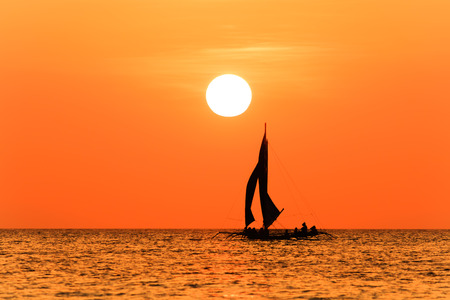 Traditional sailing boat and a tropical sunset on a calm ocean photo