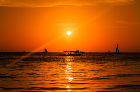 Silhouette of boats on a tropical ocean during a tropical sunset photo