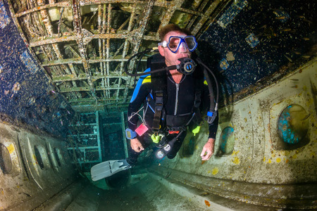 explores: A SCUBA diver explores the upturned cabin of an underwater aircraft wreck