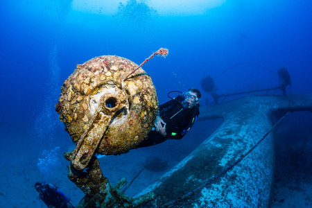 explores: SCUBA Diver explores the growth-encrusted landing gear of an underwater aircraft wreck Stock Photo