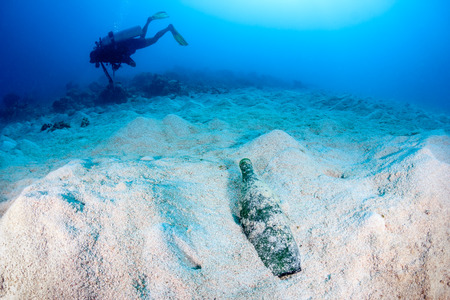 threatened: A Scuba diver swims over a dead, empty seabed next to a dumped, empty bottle