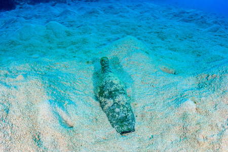 dumped: A dumped empty bottle sits on a sandy, lifeless seabed