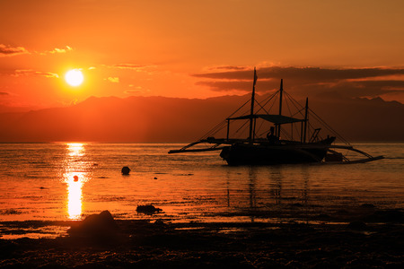 Traditional boats and mountains in silhouette against a tropical sunset photo