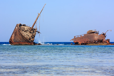 A rusting metal shipwreck aground on a tropical coral reef Stock Photo