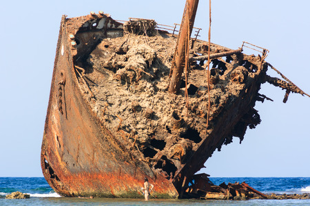 A swimmer stands next to a huge, rusting shipwreck on a tropical coral reef Stock Photo