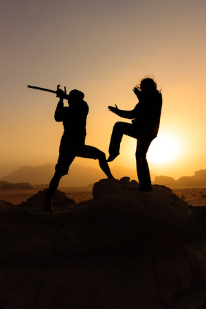 Two figures in silhouette fighting a battle against a rising sun in the desert photo