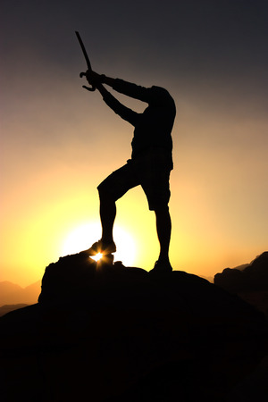 A figure holding a sword above his head in silhouette against a desert sunrise photo