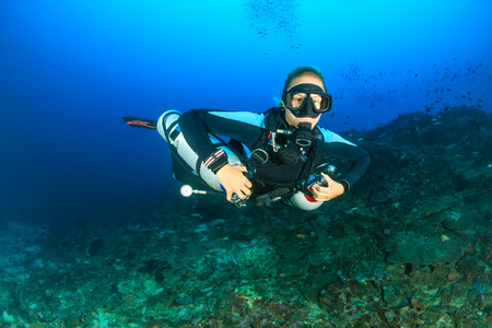girl underwater: SCUBA diver using twin sidemount tanks deep underwater Stock Photo