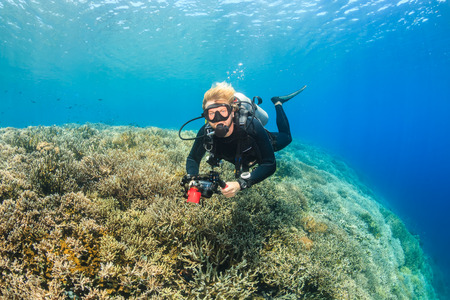 SCUBA diver with an underwater camera swims over a clear, bright tropical coral reef