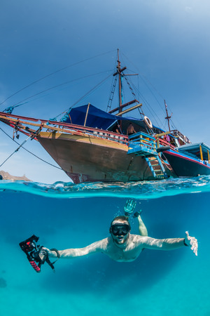 half fish: Snorkel dives under a traditional wooden boat in clear, tropical waters