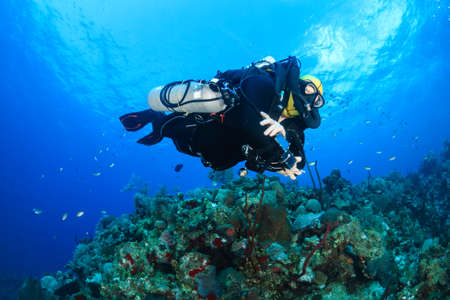 explores: SCUBA diver with an advanced Closed Circuit Rebreather explores a deep tropical coral reef
