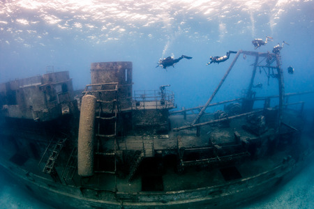 SCUBA divers around a huge underwater shipwreck Stock Photo
