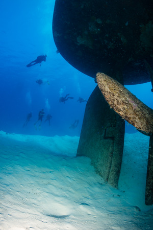 ship wreck: SCUBA Divers swim around the stern, rudder and propellor of a large underwater shipwreck