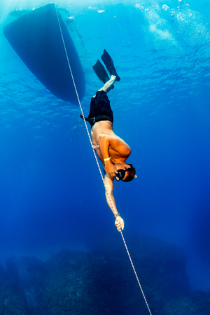 Freediver descending underneath a boat onto a reef