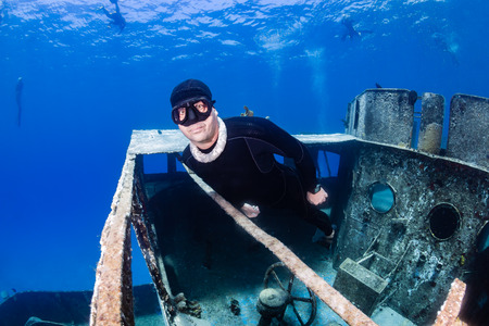 Freediver around a large underwater shipwreck