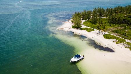 A boat near a deserted sandy beach during an algae bloom