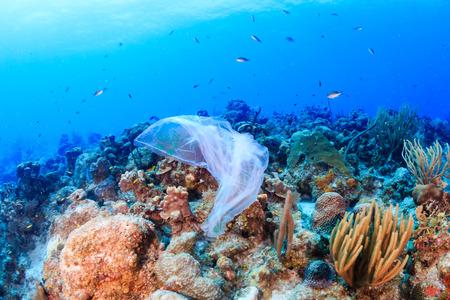 Plasticvervuiling: - een afgedankte plastic vuilniszak drijft op een tropisch koraalrif dat een gevaar vormt voor het leven in zee Stockfoto