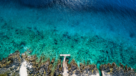 Aerial view of a small dock leading onto a tropical coral reef in crystal clear blue water Stock Photo
