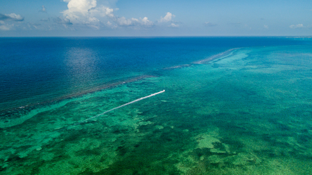 A small boat travels over a shallow, fringing tropical coral reef Stock Photo