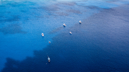 Dive boats over a large underwater shipwreck and coral reef from above