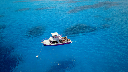 A diving boat in clear blue water over a tropical coral reef