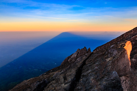 crater lake: Mount Agung volcano casts its huge shadow over the island of Bali at sunrise