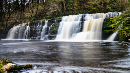 brecon beacons: Long exposure of a waterfall (Sgwd Y Pannwr) in a tree covered forest in the autumn Stock Photo