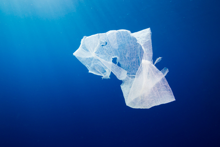 A discarded plastic bag floating in open ocean.  Plastic pollution is a rapidly growing environmental problem.