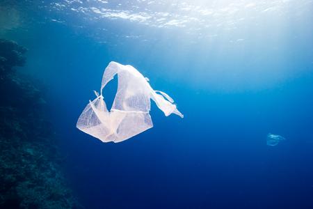 Contaminación ambiental: una bolsa de plástico desechada flota junto a un arrecife de coral tropical Foto de archivo